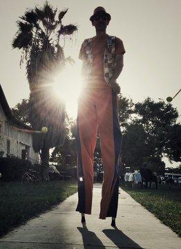 Man Walking On Stilts In Park