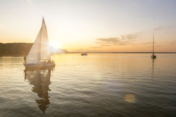 Sailing boats coming back into the harbor during beautiful sunset at the Baltic Sea