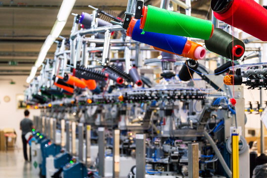 Colorful reel thread set up at modern and automatic sewing or embroidery spinning machine, textile industry factory concept