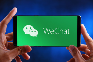Hands holding smartphone displaying logo of WeChat