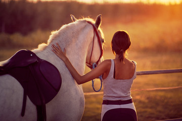 Brunette young woman and her horse . Fun on countryside, sunset golden hour. Freedom nature concept.