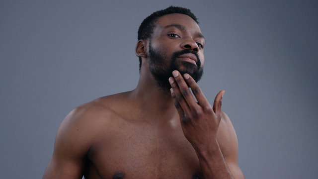 Attractive african american man portrait on grey background. Sensual sexy topless guy looking in the mirror applying perfume on his body.