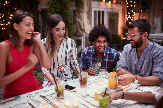 Group of young people with cocktails  having fun in nightclub celebrating. Fun, friendship, celebration concept.