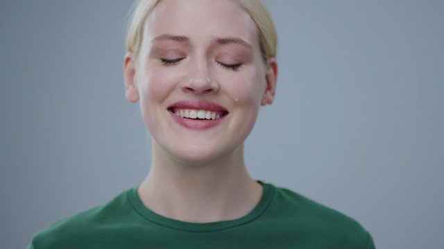 Portrait of beautiful young blonde woman crying of happiness with tears smiling on camera in the studio on grey background.