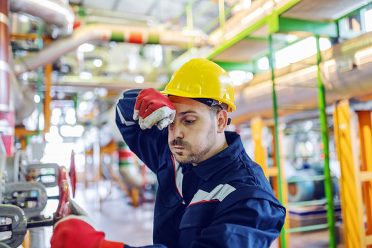 Hardworking handsome caucasian plant worker in protective suit and with helmet on head trying to screw valve while wiping sweat.