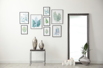 Living room interior with paintings of tropical leaves on white wall