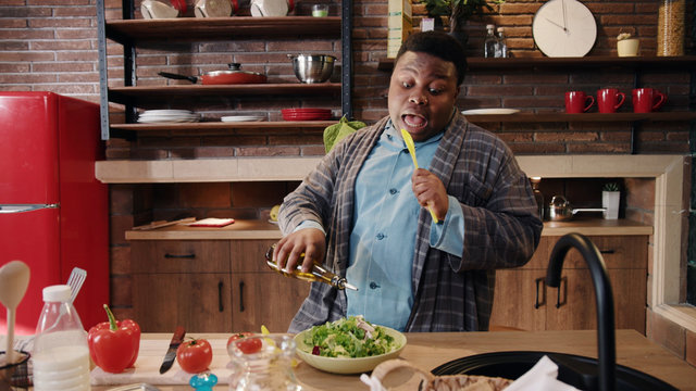 Charming cute funny young african american man cook salad dance sing in the kitchen at home look at camera preparation black food fresh fun healthy vegetables dinner portrait