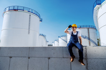 Full length of handsome caucasian workman in overalls and with helmet on head sitting on wall and looking away. In background are tanks with oil. Refinery exterior.