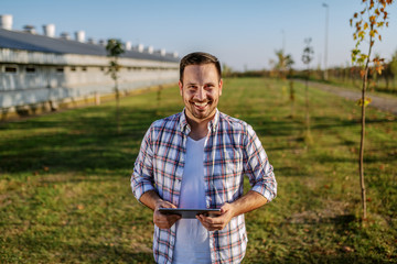 Cheerful caucasian farmer in plaid shirt standing outdoors and holding tablet. In background are barns and orchard.