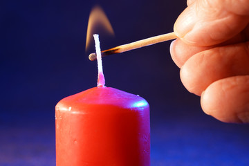 Red candle with smoke and flame photographed in the studio with color foils before the flashes