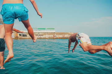 Group of happy crazy people having fun jumping in the sea water from boat. Friends jump in mid air on sunny day summer pool party at diving holiday. Travel vacation, friendship, youth holiday concept. Wall mural