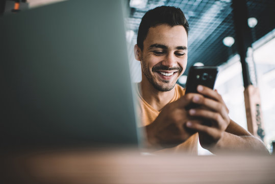 Millennial male laughing watching funny video on smartphone spending free time in cafe interior,successful man blogger satisfied with online earning getting income on banking account on cellular.