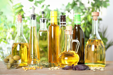 Different sorts of cooking oil in bottles on wooden table