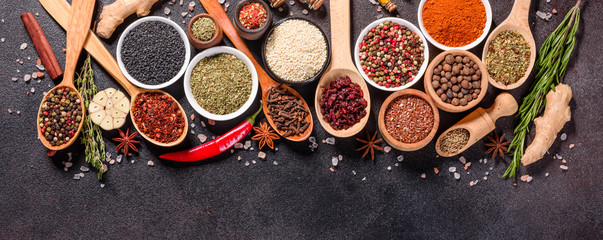 Spices and herbs over black stone background. Top view with free space for menu or recipes