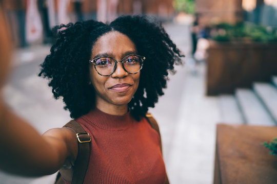 Young black woman smiling and taking selfie