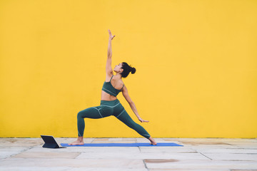 Photo sur Plexiglas Ecole de Yoga Sporty woman learning yoga with tablet outside