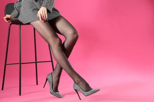 Woman wearing black tights and stylish shoes on pink background, closeup of legs