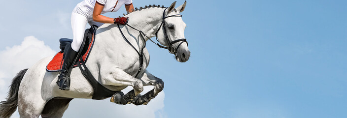 Girl jumping with white horse, isolated, blue sky, white clouds background. Rider in white uniform, equestrian sports. Horizontal header or banner. Ambition, breaking through, free, health concept.
