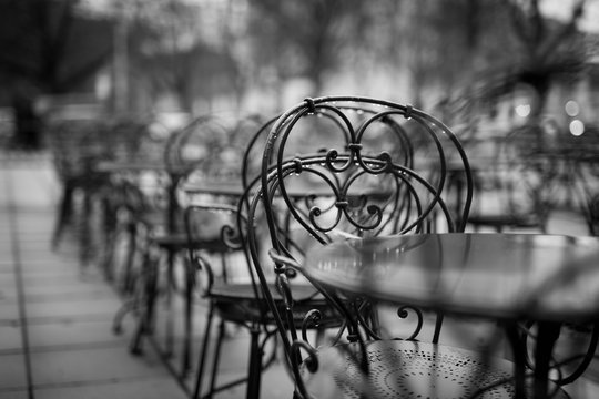 Wet Tables And Chairs Of Sidewalk Cafe In Rain