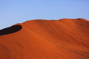 In de dag Rood traf. Beautiful landscape with red huge sand dunes at sunset in desert. Sossusvlei, Namib Naukluft National Park, Namibia. Stunning natural geometry without people