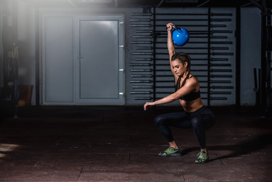 Young beautiful attractive muscular and strong fit girl holding heavy kettlebell with one hand above her head for swing or snatch hardcore crossfit workout training in the gym real people