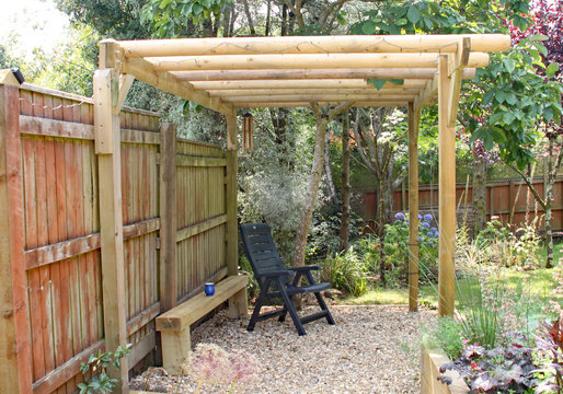 A quiet relaxing and shady area in a back garden under a pergola and magnolia tree