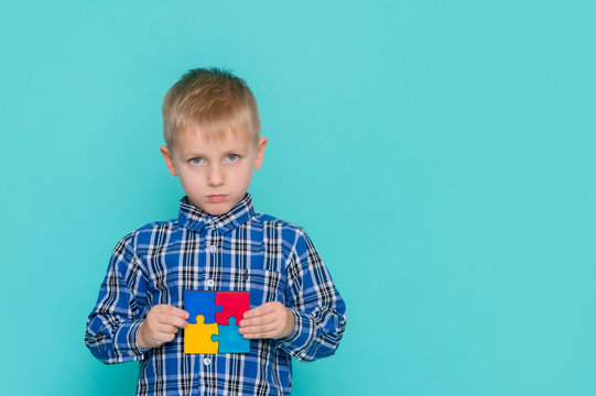 A little child holding a puzzle symbol of Public awareness for autism spectrum disorder. World Autism Awareness Day.