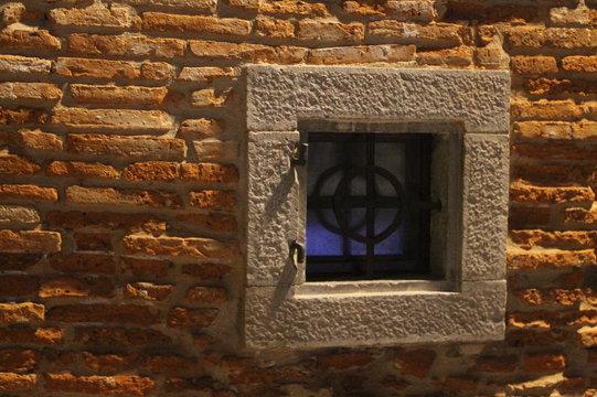 inferriata in ferro battuto a croce celtica, finestra con cornice in pietra