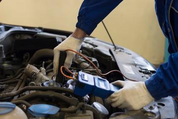 A professional mechanic diagnoses a car in a car service. Measurement of compression of a car engine.