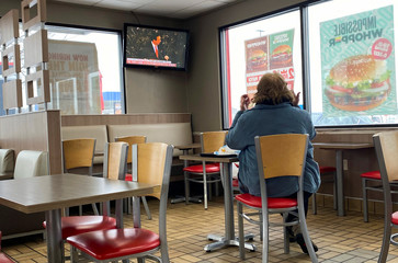 A woman eats in a fast food restaurant as a tv shows President Trump's impeachment trial in Des Moines, Iowa