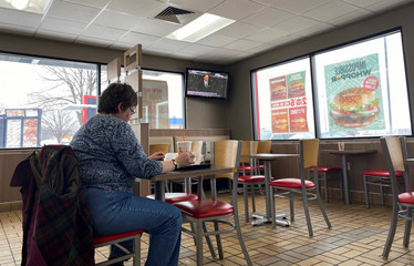 A woman eats in a fast food restaurant as a tv shows President Trump's Senate impeachment trial in Des Moines, Iowa