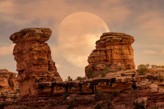 Full moon at it's perigee rising in Maze District at  Canyonlands National Park during sunset