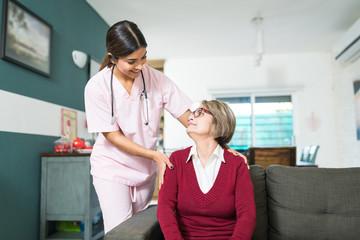 Caregiver Taking Care Of Elderly Female At Home