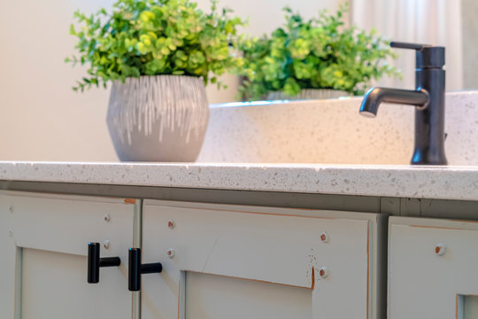 White countertop with balck faucet and sink supported by vanity cabinets