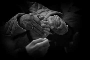 Close-Up Of People Praying By Holding Hands Fotomurales