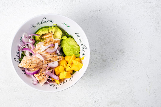 Grilled chicken, mango and avocado salad in deep salad bowl on light background, top view