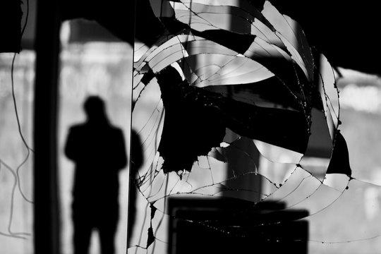 Reflection Of Silhouette Man On Broken Mirror