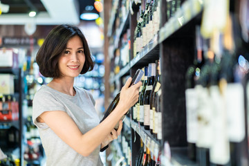 Young Asian beautiful casual cloth woman holding shopping in supermarket. She is choosing nice red wine bottle picking up from alcohol shelf at wine store shop while she looking at camera and smile.