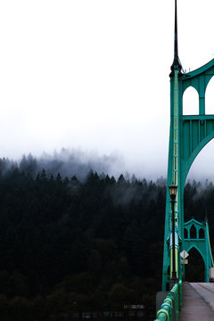 Cropped Image Of St Johns Bridge By Trees Against Sky During Foggy Weather
