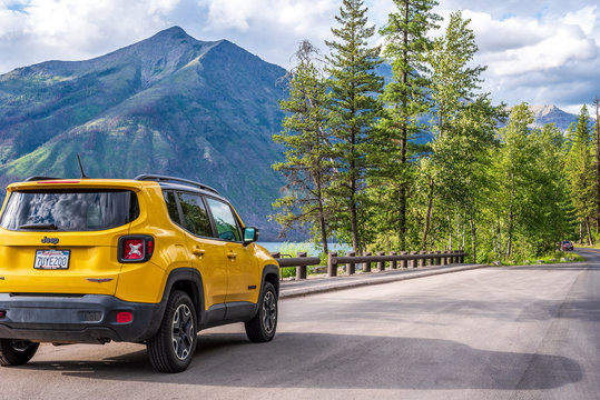 West Glacier, Montana/USA – July, 18 2019: Yellow Jeep parked along the Going to the Sun road in Glacier National Park with mountain range in background