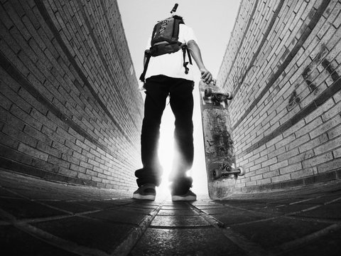 Low Angle View Of Man Holding Skateboard While Standing On Footpath