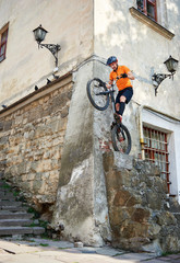 Young stuntman getting ready to jump with his mountain bike from the corner of ancient building, concept of extreme sport