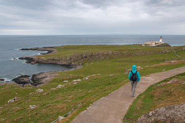 Unrecognizable tourist, wearing a jacket to protect himself from the wind, walking towards the Neist Point lighthouse, isle of Skye, Scotland. Concept: Scottish landscape, tranquility and serenity