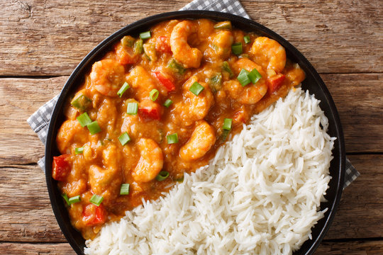 Spicy traditional shrimp Etouffee with celery, onion and pepper with sauce served with rice closeup in a plate. Horizontal top view