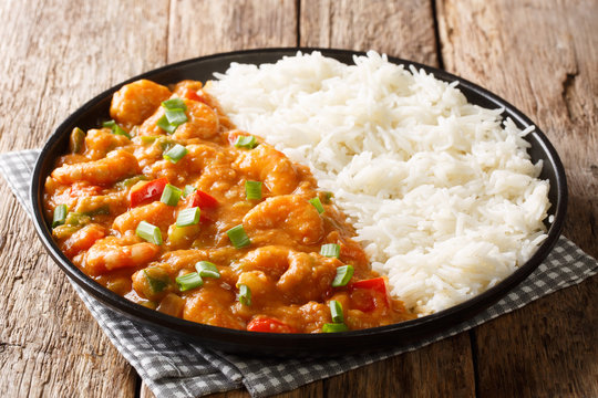 Serving of shrimp Etouffee with vegetables and sauce served with rice closeup in a plate. horizontal