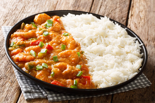 Spicy traditional shrimp Etouffee with celery, onion and pepper with sauce served with rice closeup in a plate. horizontal