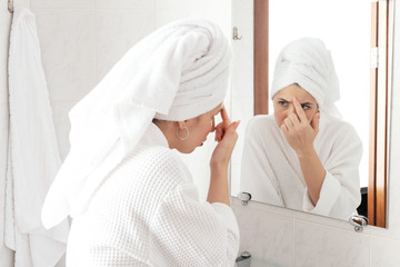 Keuken foto achterwand Bakkerij Beautiful middle-aged brunette looking at mirror and touching wrinckles on her forehead. Anti aging treatment prevention cream using
