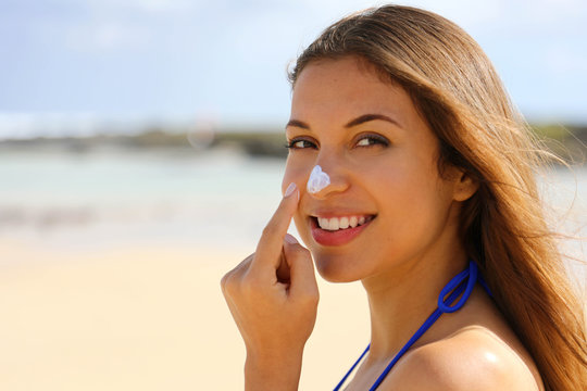 Close up young beautiful woman applying sun cream protection on her nose on the beach. Suntan lotion woman applying sunscreen solar cream.