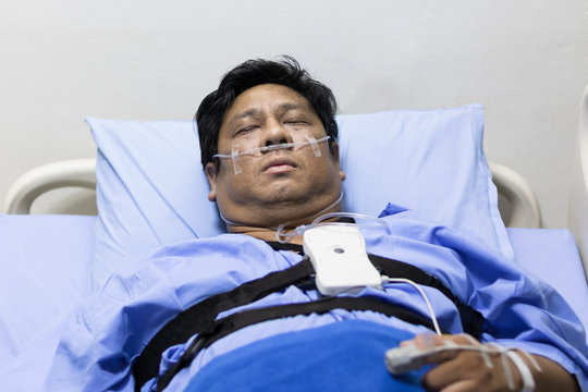 Asian Fat Man Sleeping On A Patient Bed With Breathing Equipment in Hospital.