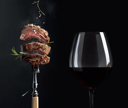 Grilled  beef steak with rosemary and glass of red wine on a black background.